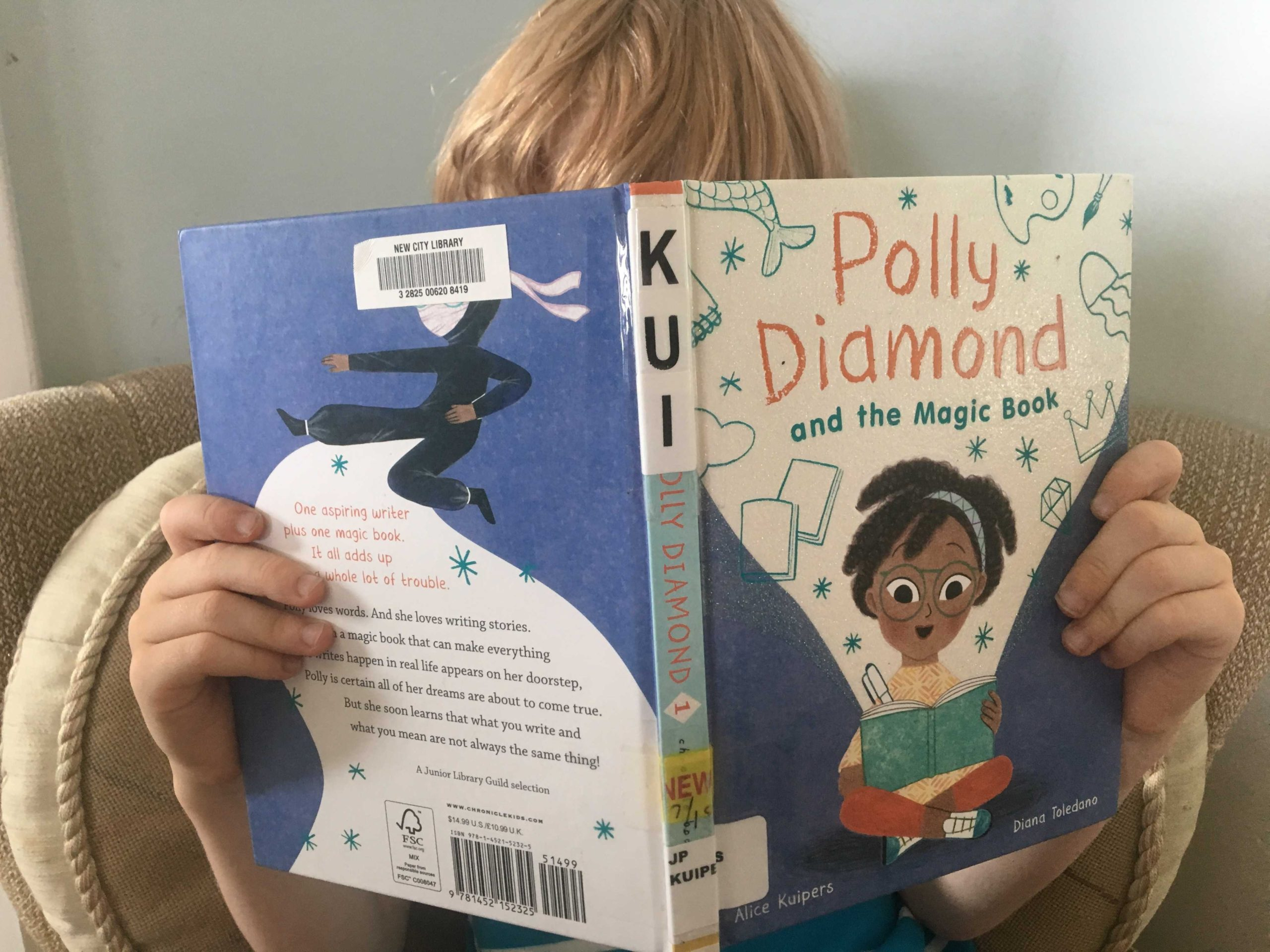 Blonde kid reading a book about an African American girl.